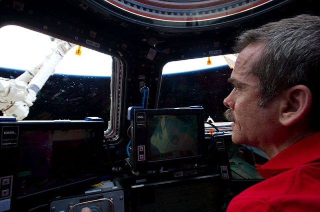 Chris Hadfield inside the ISS cupola manipulating the Canada Arm