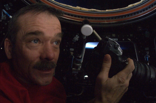 Cmdr Chris Hadfield at the coupole aboard the ISS taking Twitter photos of Earth