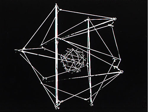 Original photograph of a stick-and-string tensegrity model containing a smaller tensegrity at its center that is connected to the surface by black elastic thread (not visible against black background), which Ingber used to present his cellular tensegrity theory.  This model is unanchored and therefore both the 'cell' and 'nucleus' take on round forms, much as observed in living cells. [Image: Don Ingber.]