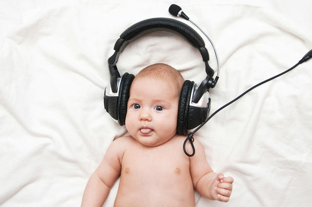 Adorable little girl lying in headphones